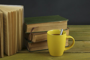 Old vintage books and cup  on wooden table