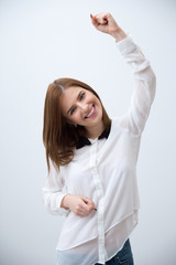 Happy young woman celebrating success over gray background