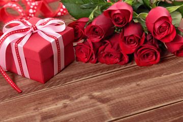 Valentine background of gift box and red roses on wood. Space fo