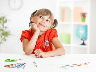 Smiling cute schoolgirl dreaming making homework. Creation