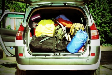 car with the trunk full of luggage and suitcases