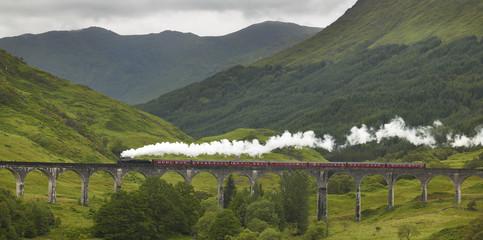 Scottish steam train passing a classic bridge