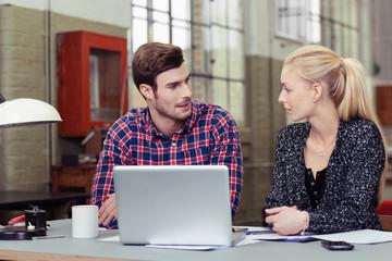 motivierte junge leute mit laptop am schreibtisch