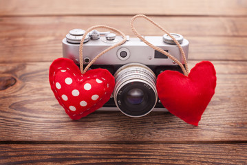 Retro Camera with red hearts on wooden background.