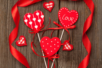 Variety of red hearts with ribbons on vintage wooden background