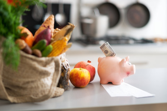 Closeup on money in piggy bank and purchases from local market