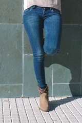 Legs of urban girl with jeans and boots standing in front of a s
