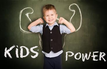Kind mit Kraft vor Tafel und Muskeln