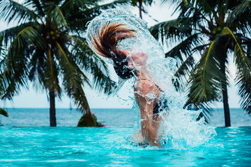 Sexy woman doing hairflip in swimming pool