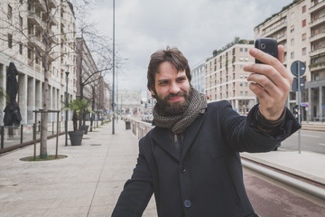 Young handsome bearded man taking a selfie in the city streets