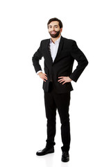 Smiling businessman with hands on hips.