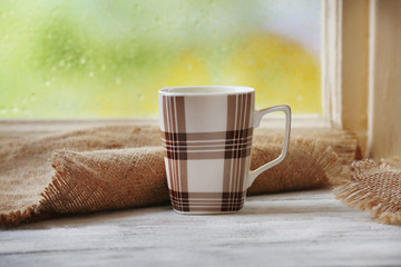 Cup of hot drink with sackcloth on windowsill on rain