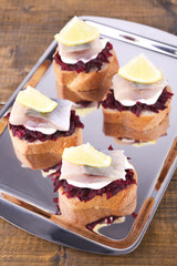Rye toasts with herring and beets on tray on wooden background