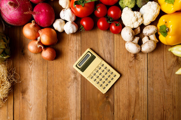 Calculator with vegetables on a Wooden Background