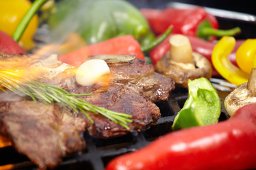 T-bone steak on the barbecue grill with vegetable spears in the