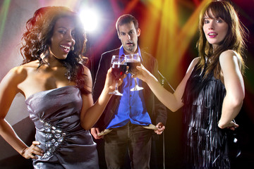 women seducing a man to buy them cocktails at a nightclub