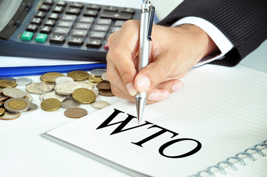 Hand with pen pointing to WTO (World Trade Organization)