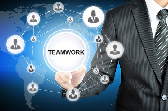 Businessman hand pointing on TEAMWORK sign on virtual screen