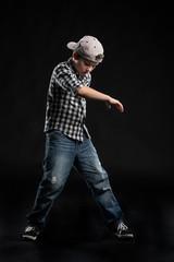 little break dancer showing his skills on black background.