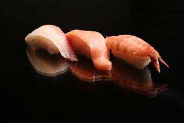 tasty sushi and sashimi on black background
