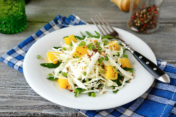 Fresh cabbage salad and orange on a plate