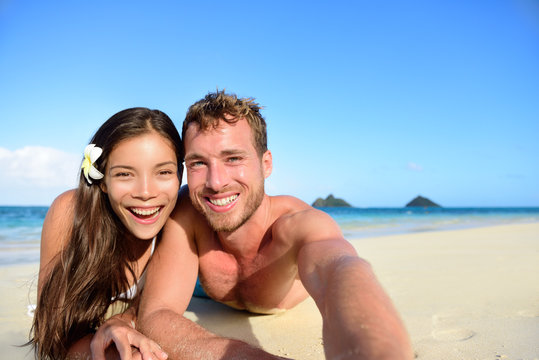 Couple relaxing on beach taking selfie picture