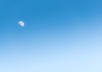 the moon in the day on blue sky