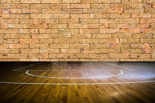 wooden floor basketball court with red brick wall texture backgr