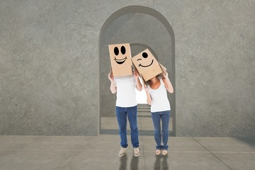 Composite image of mature couple wearing boxes over their heads