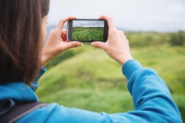 Hiker woman taking photographs summer landscape