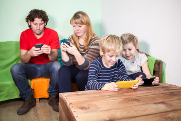 All family having fun with the games on smartphones