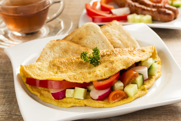 a nice omelet  with vegetables, on the table
