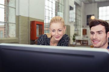 zwei junge leute schauen auf computer-bildschirm