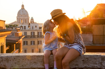 Mother and baby girl kissing while sitting on street  in Rome