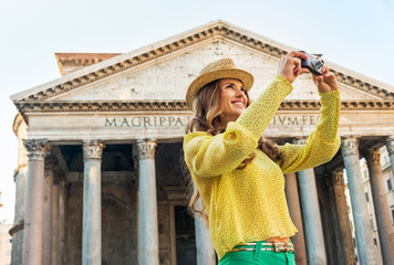 Happy young woman taking photo in front of pantheon in rome