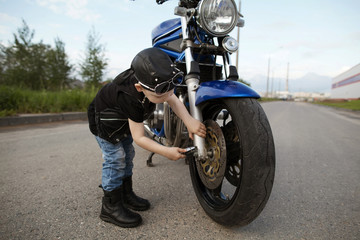 little biker repairs motorcycle on road