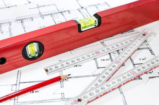 Wasserwaage, Stift und Zollstock auf einem Bauplan/Grundriss liegend