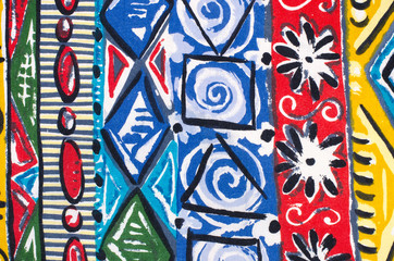 Abstract flowers and geometric shapes print on colorful fabric.