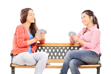 Teenage sisters playing cards seated on a bench