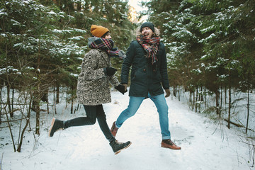 Young hipster couple jumping in winter forest