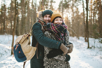 Young man hugs his girlfriend in winter forest