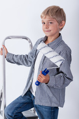Child holding paint roller
