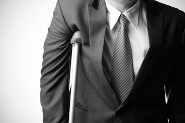 injured businessman with crutches, insurance concept