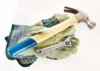 Hammer with an adjustable wrench lie on protective gloves