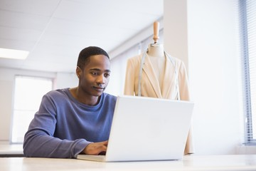 Smiling university student using laptop