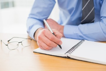 Businessman taking notes on notebook
