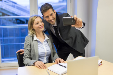 Two business people making a Selfie in the office