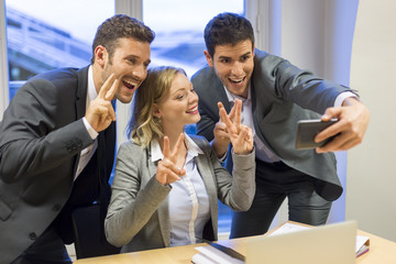 Three business people making a happy Selfie in office