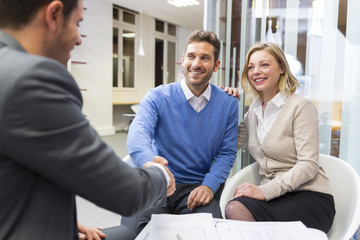 Young couple shaking hand real-estate agent in agency office