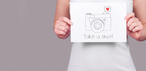 Photography concept, woman holding camera drawing with text